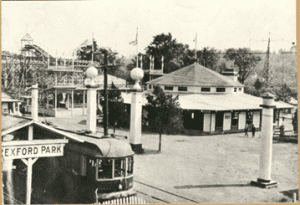 Trolley stop, Rexford Amusement Park, c. 1920. Roller coaster and merry-go-round just inside the main entrance to the park