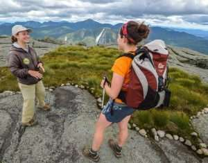 ADK summit steward talking to hiker in alpine zone in adirondacks